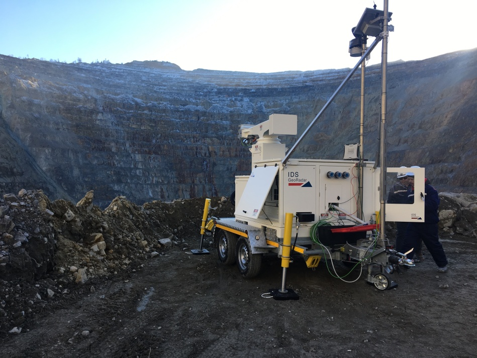 A slope monitoring device perched on the edge of a mining pit