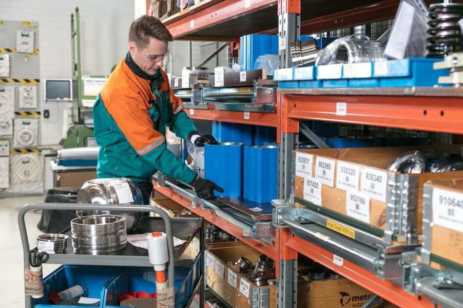 A storeman sorts through spare parts on a shelf